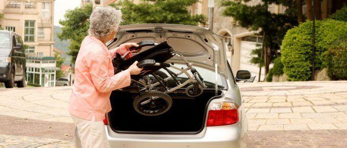 Mujer mayor introduciendo una silla de ruedas en el maletero